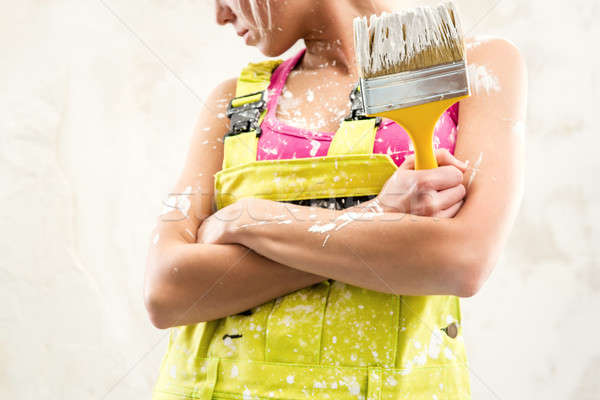 Female in coverall holding paint brush over obsolete white wall Stock photo © amok