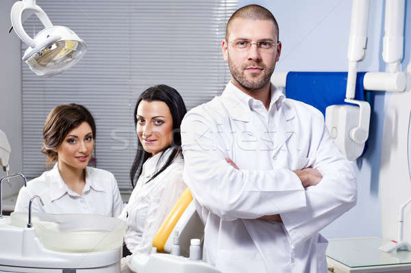 Friendly male dentist, assistant and smiling patient  Stock photo © amok