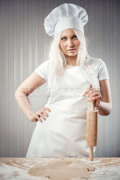 Woman holding rolling pin wearing uniform posing indoors Stock photo © amok