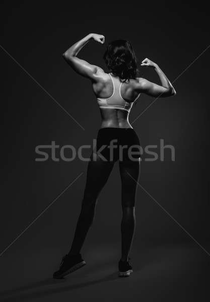 Athletic woman showing back and biceps muscles.  Stock photo © amok
