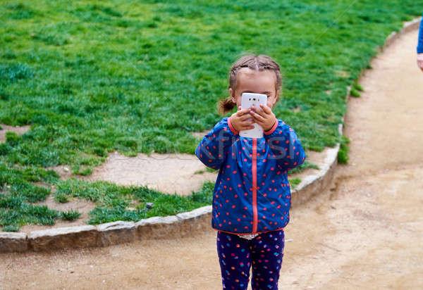 Petite fille vidéo photo téléphone portable extérieur Photo stock © amok