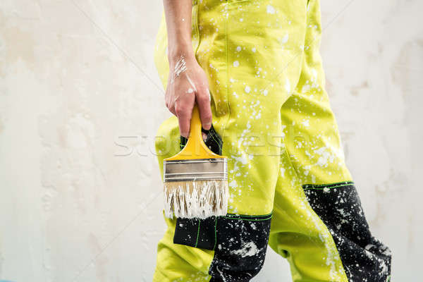 Female hand with paint brush over white obsolete background Stock photo © amok