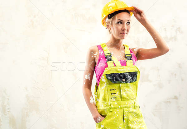 Female construction worker posing over white obsolete wall Stock photo © amok