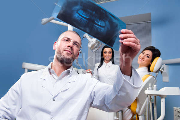 Dentist with x-ray and smiling patient and assistant  Stock photo © amok