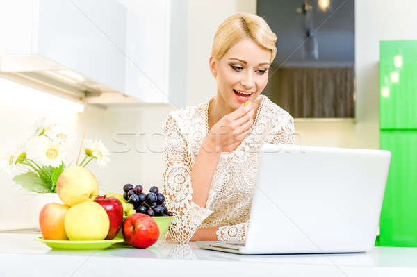 Beautiful young woman using her laptop computer in the kitchen Stock photo © amok