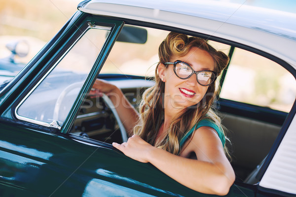 Beautiful happy woman sitting in a car. Retro styled Stock photo © amok