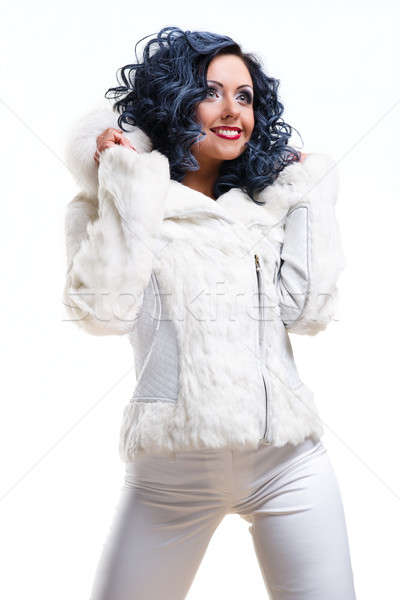 Cheerful brunette in white fur coat posing over white background Stock photo © amok