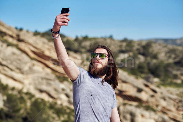Young man traveler with a beard and long hair taking selfie photo Stock photo © amok
