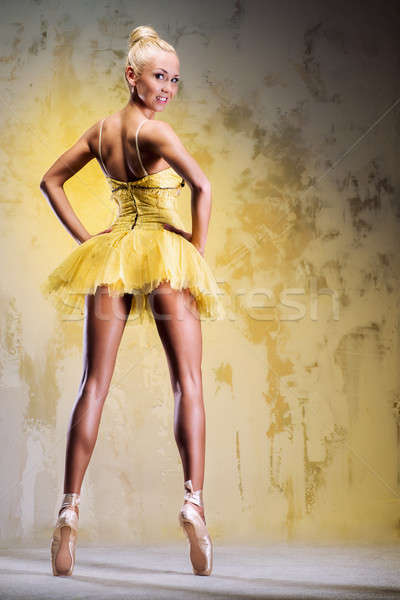 Beautiful ballerina in yellow tutu on point posing over obsolete wall Stock photo © amok