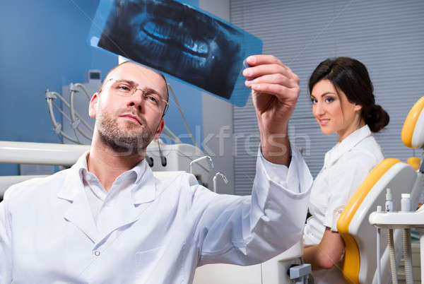 Dentist with x-ray and smiling patient in the background  Stock photo © amok