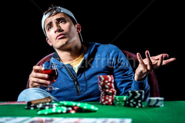 Young gambler holding glass of cognac  Stock photo © amok