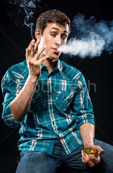 молодым человеком курение сигарету здоровья дым джинсов Сток-фото © amok