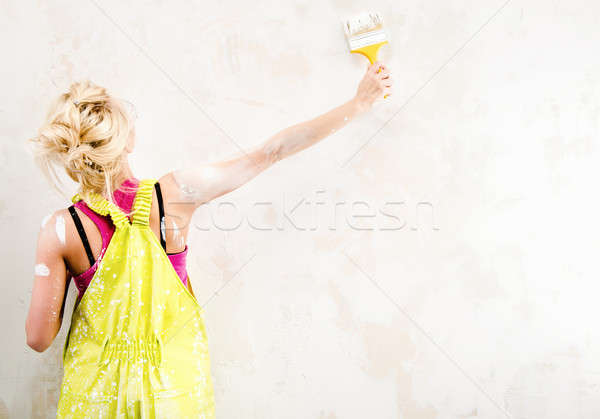 Female construction worker in coverall painting a wall  Stock photo © amok