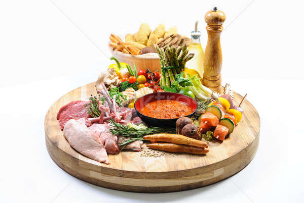 Abundance of raw food on a wooden board and basket of bread over Stock photo © amok
