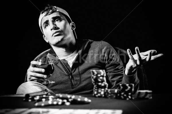 Stock photo: Young gambler holding glass of cognac, black and white photo