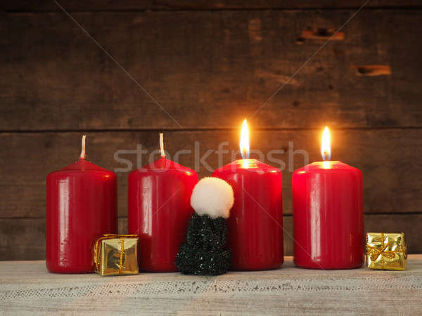 Four red candles on a wooden background Stock photo © andreasberheide