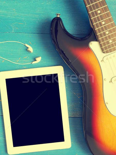 Vintage guitar with earphones on wood Stock photo © andreasberheide