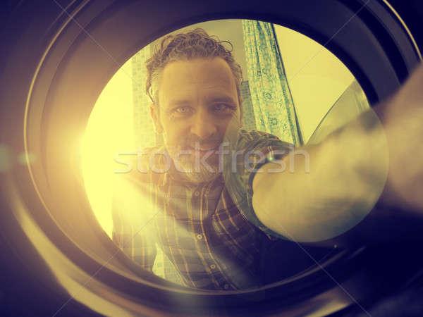 Happy man loading washing machine Stock photo © andreasberheide
