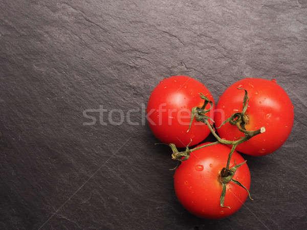 Fresh organic tomatoes on dark slate Stock photo © andreasberheide