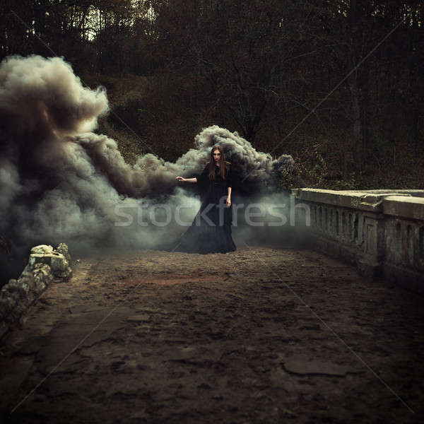 woman walking on the bridge in heavy black smoke Stock photo © andreonegin