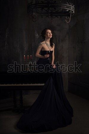 beautiful young woman in black dress next to a piano with candelabra candles and wine, dark dramatic Stock photo © andreonegin