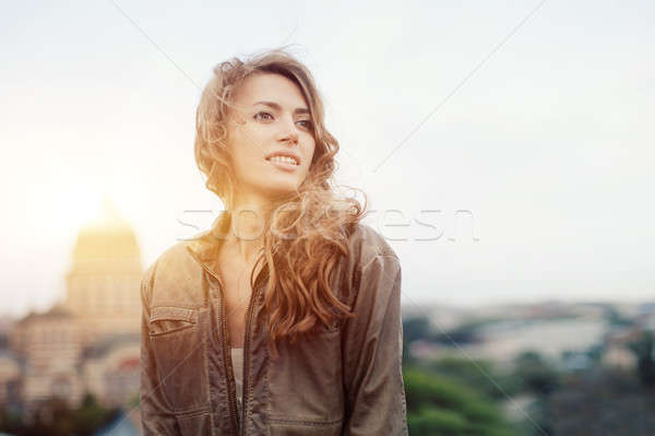 Young attractive woman with good mood enjoying beautiful city landscape while standing on a roof of  Stock photo © andreonegin