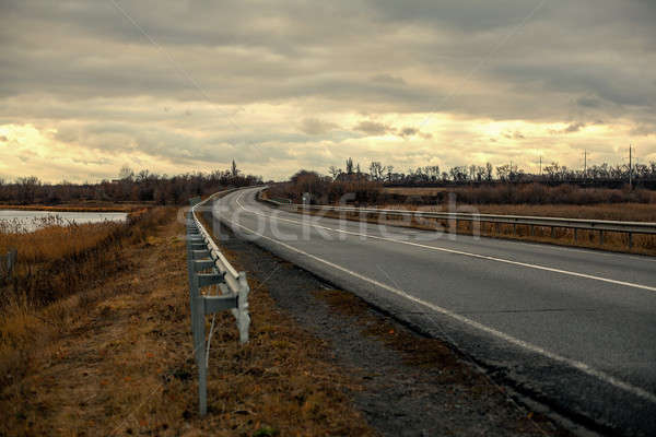 Empty asphalt road with near the lake with cloudy sky in evening light Stock photo © andreonegin