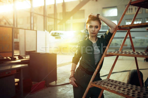 Portrait of modern young woman working in engineering standing by jet plane near the stairs looking  Stock photo © andreonegin