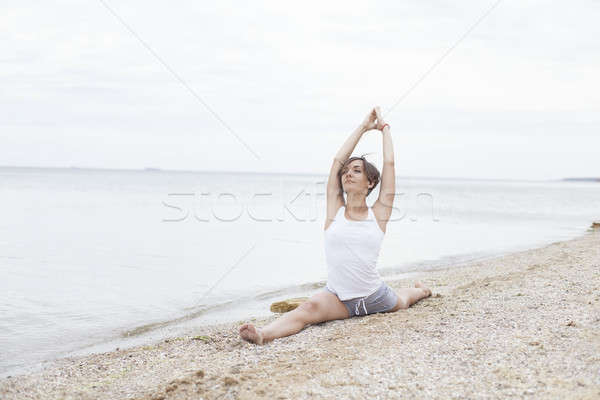 Beautiful girl practicing yoga on the beach near the sea. Sits on a twine, does a stretching. Stock photo © andreonegin