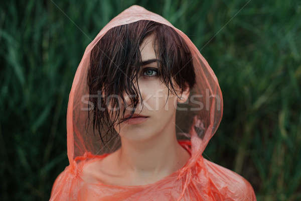 The portrait of girl in red raincoat under the rain. Stock photo © andreonegin