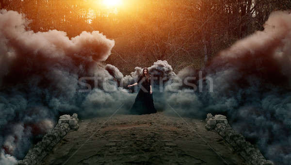 Young attractive Witch walking on the bridge in heavy black smoke. Stock photo © andreonegin