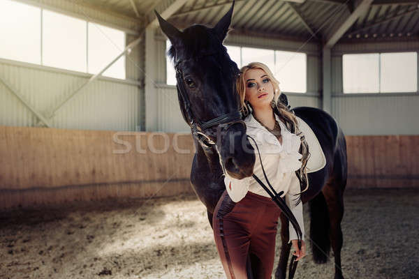 Beautiful elegant young blonde girl standing near her horse dressing uniform competition Stock photo © andreonegin