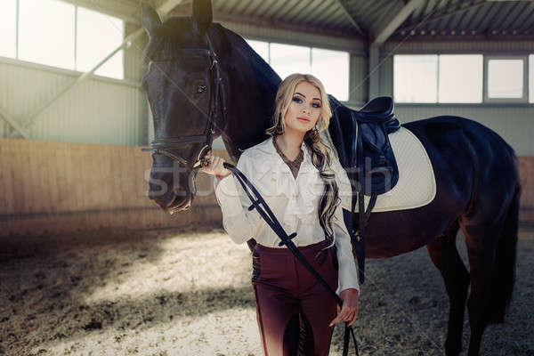 Stock photo: Beautiful elegant young blonde girl standing near her horse dressing uniform competition