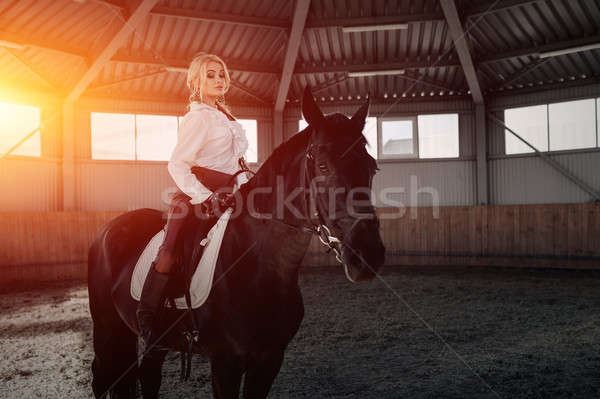 Beautiful elegant young blonde girl sits on a her black horse dressing uniform competition white blo Stock photo © andreonegin