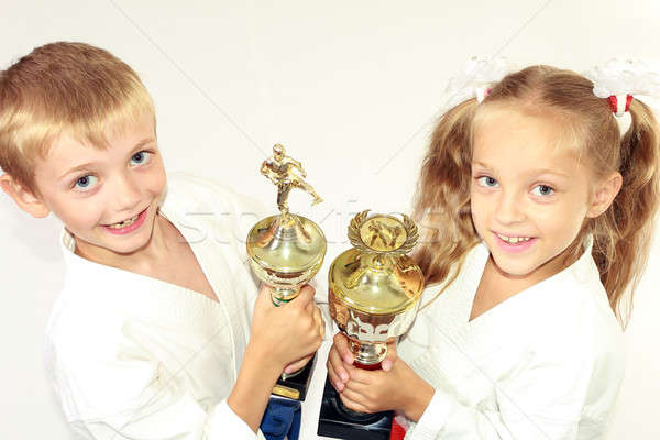Girl and boy in a kimono with a championship winning in hand on white background Stock photo © Andreyfire