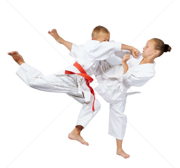 Punch in the jump and kick leg are beating the sportsmens in karategi Stock photo © Andreyfire