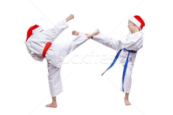 The boys in caps of Santa Claus beat kick leg Stock photo © Andreyfire