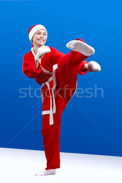 Beautiful girl dressed as Santa makes a karate kick left foot Stock photo © Andreyfire