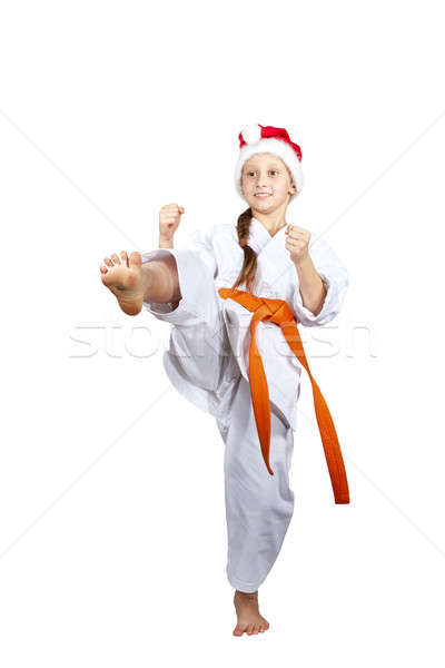 The cheerful girl in a Santa Claus cap beats kicking Stock photo © Andreyfire