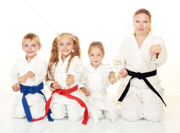 Mom with her daughter and a boy sitting with his sister in a ritual pose karate and beat his fist Stock photo © Andreyfire