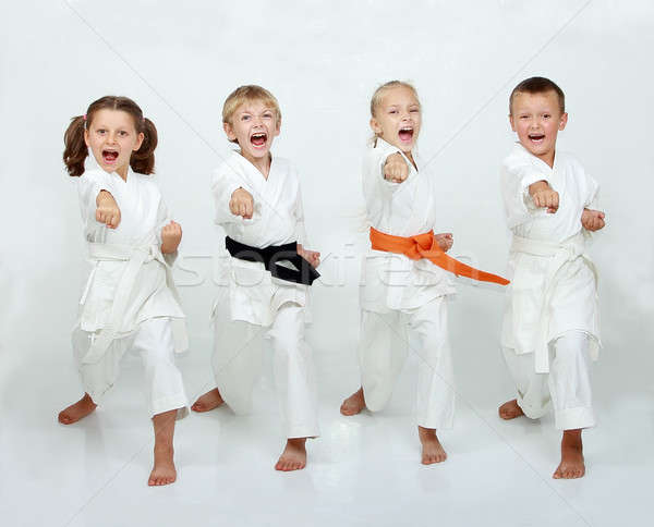 Two boys and two girls are hitting punch arm Stock photo © Andreyfire