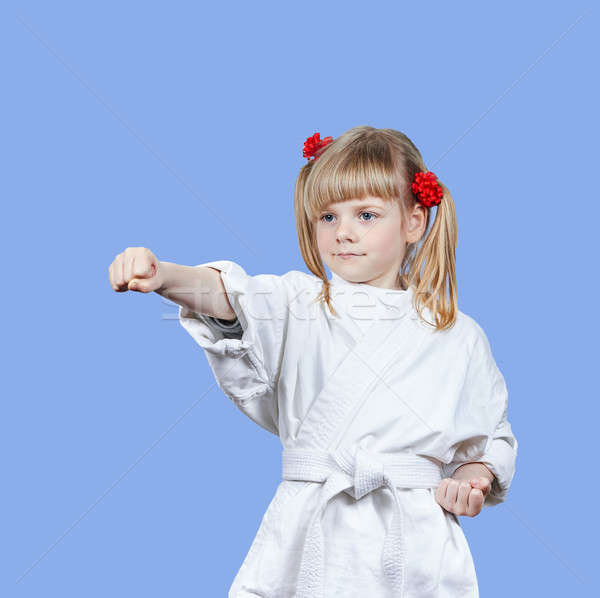On a blue background sportswoman beats punch arm Stock photo © Andreyfire