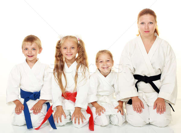 Stock photo: A boy with his sister and mother with her daughter sitting in a karate pose ritual