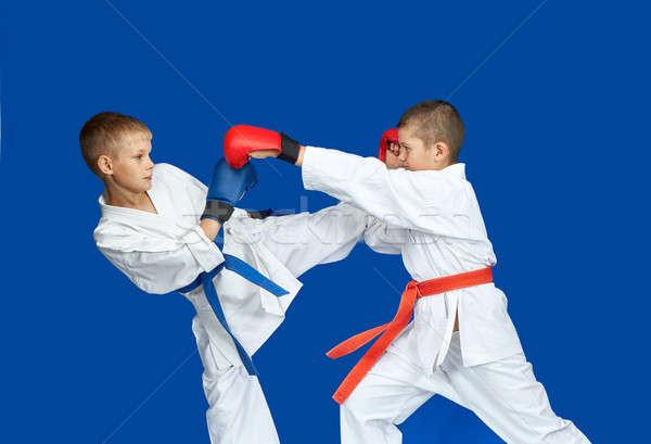 Boys in karategi are beating kick hand and leg Stock photo © Andreyfire