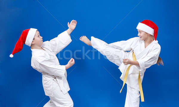 Cheerful children in cap of Santa Claus are training karate techniques Stock photo © Andreyfire