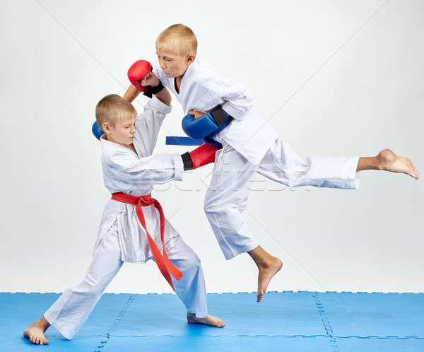 Boys in karategi are training punch in jump Stock photo © Andreyfire