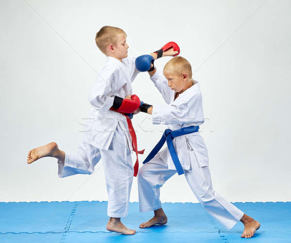 With blue and red overlays on his hands athletes train paired exercises karate Stock photo © Andreyfire