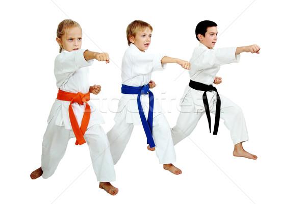 Three karateka in kimono hit a punch arm Stock photo © Andreyfire