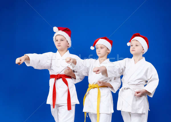 Three sportsmen in caps of Santa Claus beats punch hand Stock photo © Andreyfire