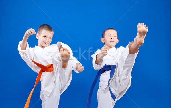 Kick leg forward athletes are beating in karategi Stock photo © Andreyfire